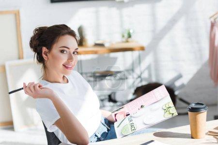 Photo pour Femme gai dans le magazine blanc de fixation de t-shirt et stylo près de tasse de papier sur la table - image libre de droit