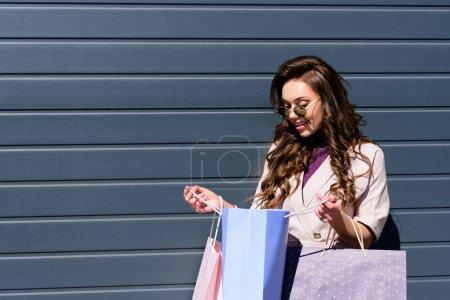 joyeuse jeune femme bouclée regardant sac à provisions bleu