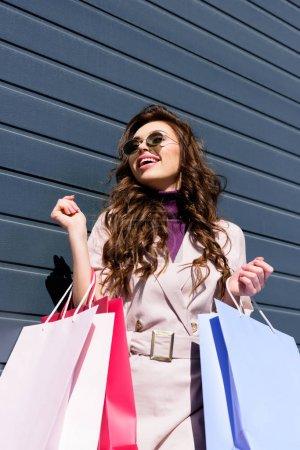 Photo pour Vue d'angle bas de femme bouclée gaie dans des lunettes de soleil restant avec des sacs à provisions - image libre de droit