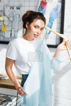 Photo for Attractive young woman holding hanger with blue dress - Royalty Free Image