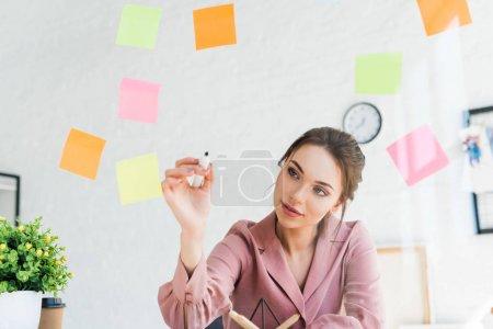 Photo pour Attrayant jeune femme écrit sur la fenêtre avec des notes collantes - image libre de droit