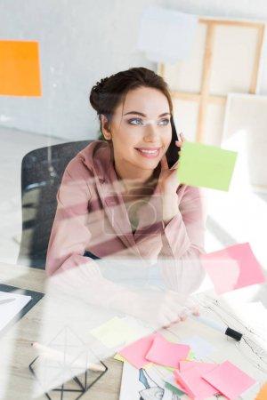 Photo pour Foyer sélectif de femme heureuse parler sur smartphone dans le bureau - image libre de droit