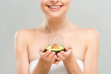 Photo for Cropped view of cheerful woman holding half of ripe avocado isolated on grey - Royalty Free Image