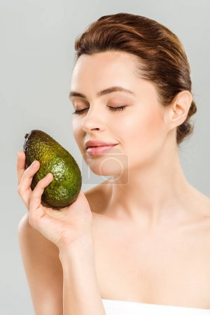 Photo for Happy woman with closed eyes holding ripe avocado isolated on grey - Royalty Free Image