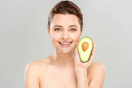 Photo for Cheerful naked woman holding half of organic and ripe avocado isolated on grey - Royalty Free Image