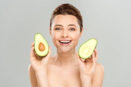 Photo for Happy naked woman holding halves of organic avocado isolated on grey - Royalty Free Image