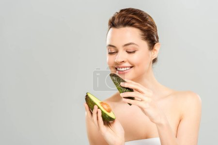 Photo for Happy woman holding halves of organic avocado isolated on grey - Royalty Free Image