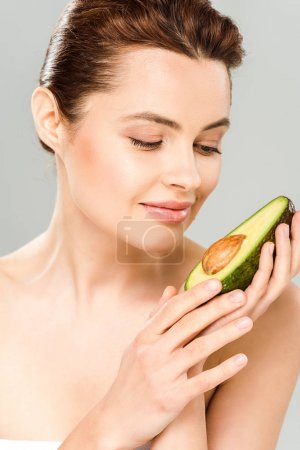 Photo for Happy woman looking at half of ripe avocado isolated on grey - Royalty Free Image
