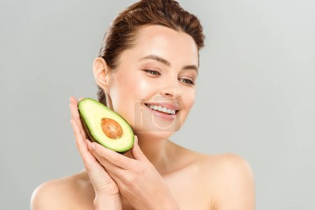 Photo for Happy and naked woman holding half of ripe avocado isolated on grey - Royalty Free Image
