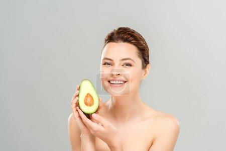 Photo pour Femme attirante et nue retenant la moitié de l'avocat mûr et souriant d'isolement sur le gris - image libre de droit