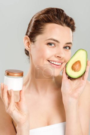 Photo for Happy woman holding half of avocado and container with cosmetic cream isolated on grey - Royalty Free Image