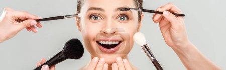 Photo pour Plan panoramique de maquilleurs tenant des pinceaux cosmétiques près de femme excitée isolée sur gris - image libre de droit