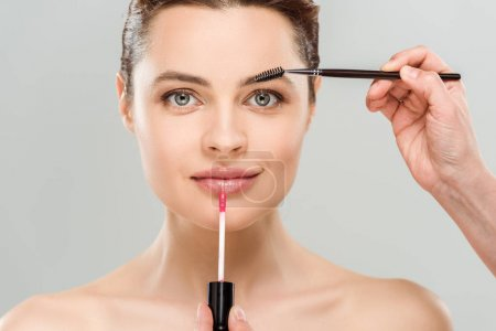 Photo for Cropped view of makeup artist holding mascara brush and lip gloss near naked woman isolated on grey - Royalty Free Image