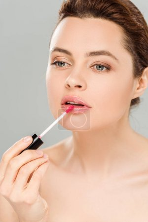 Photo for Attractive naked woman applying lip gloss on lips isolated on grey - Royalty Free Image