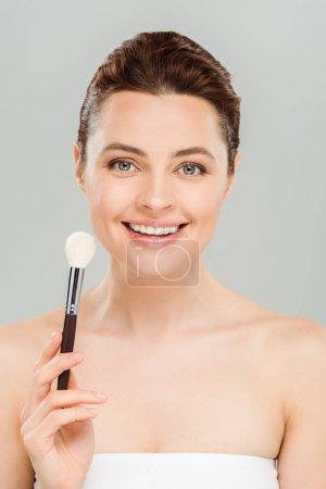 Photo pour Femme gaire retenant le pinceau cosmétique et souriant d'isolement sur le gris - image libre de droit