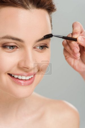 Photo for Cropped view of makeup artist holding eyebrow brush near cheerful naked woman isolated on grey - Royalty Free Image