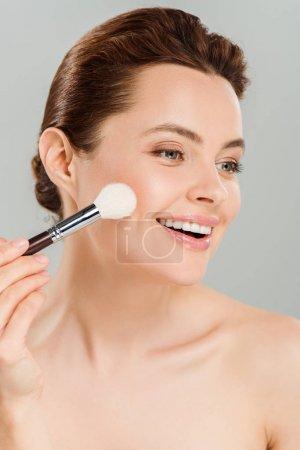 Photo pour Femme gaie appliquant le fard à joue avec le pinceau cosmétique et souriant isolé sur le gris - image libre de droit