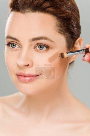 Foto de Mujer atractiva sosteniendo cepillo cosmético y aplicando rubor marrón en la mejilla aislada en gris - Imagen libre de derechos