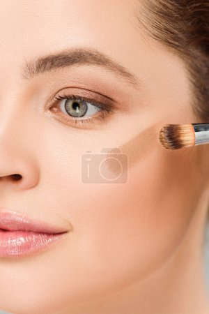 Photo for Cropped view of woman holding cosmetic brush and applying brown blush on cheek isolated on grey - Royalty Free Image