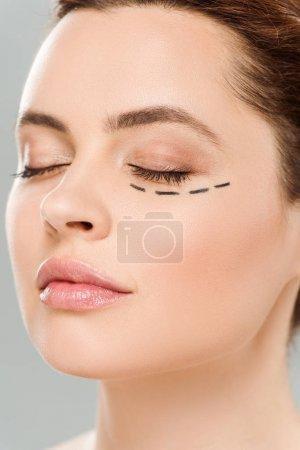 Photo pour Fermez vers le haut la vue de la belle femme avec les yeux fermés et marques sur le visage isolé sur le gris - image libre de droit