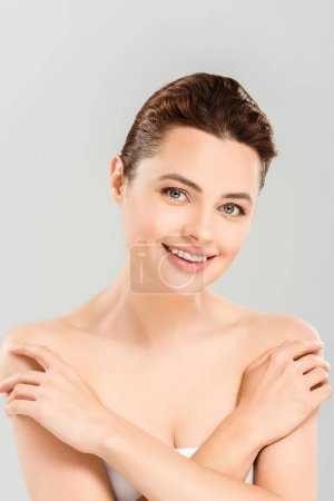 Photo for Cheerful woman touching shoulders and smiling isolated on grey - Royalty Free Image