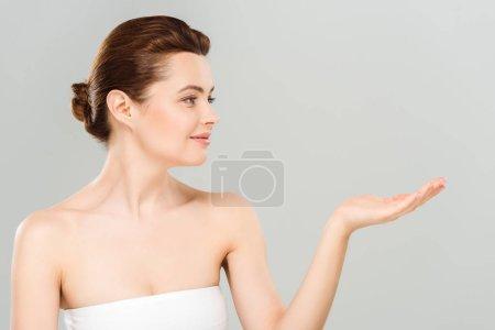 Photo pour Femme gaie et attrayante gestuelle et souriante isolée sur gris - image libre de droit