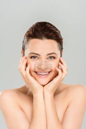 Photo pour Femme attirant souriant tout en touchant le visage d'isolement sur le gris - image libre de droit