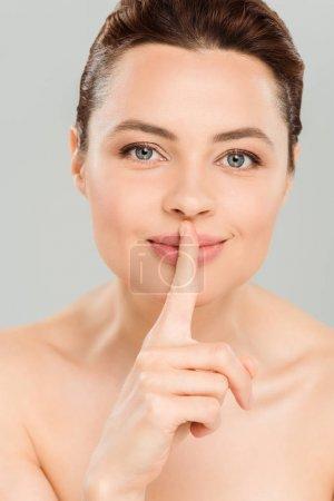 Photo pour Femme nue heureuse affichant le signe de silence et souriant d'isolement sur le gris - image libre de droit