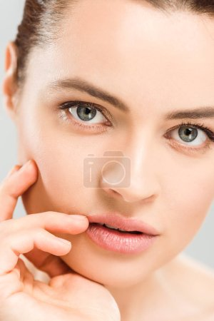 Photo for Close up of serious woman looking at camera and touching face isolated on grey - Royalty Free Image