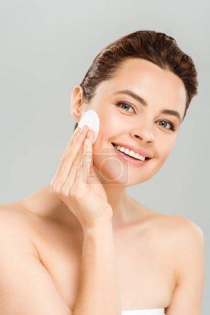 Photo pour Femme positive retenant le tampon de coton près du visage et souriant isolé sur le gris - image libre de droit