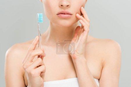 Photo pour Vue recadrée de femme touchant le visage et retenant la brosse à dents d'isolement sur le gris - image libre de droit