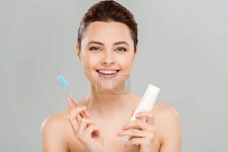 Photo pour Femme positif souriant tout en retenant la brosse à dents et le tube avec le dentifrice d'isolement sur le gris - image libre de droit
