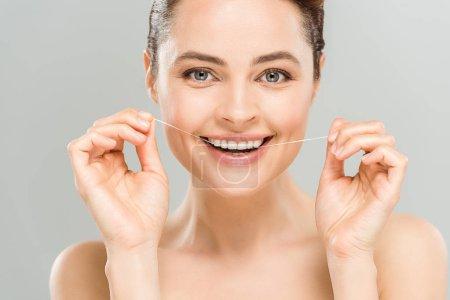 Photo pour Heureux nu femme fil dentaire dents avec fil dentaire isolé sur gris - image libre de droit