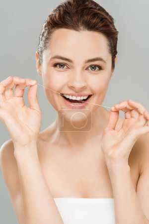 Photo for Happy woman flossing teeth with dental floss isolated on grey - Royalty Free Image