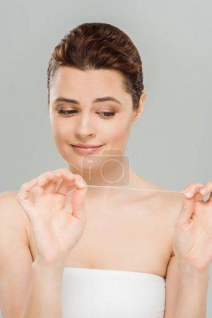 Photo pour Femme attirante regardant la soie dentaire d'isolement sur le gris - image libre de droit