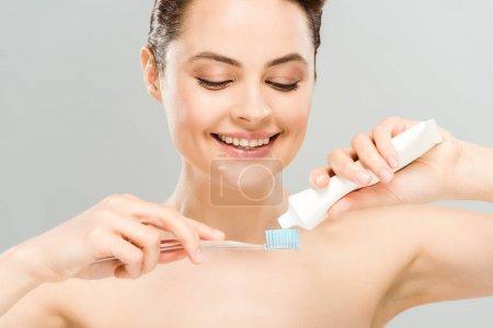 Photo pour Femme nue gaie retenant le dentifrice près de la brosse à dents d'isolement sur le gris - image libre de droit