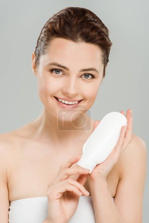 Photo pour Bouteille heureuse de fixation de femme de lotion de corps d'isolement sur le gris - image libre de droit