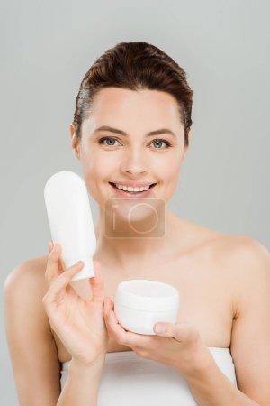 Photo pour Récipient gai de fixation de femme avec la crème cosmétique et la bouteille de lotion de corps d'isolement sur le gris - image libre de droit