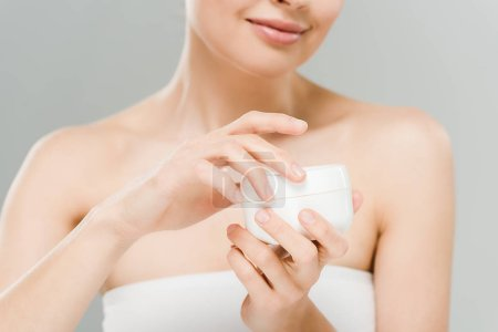 Photo for Selective focus of woman holding container with face cream isolated on grey - Royalty Free Image
