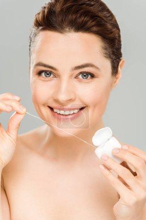 Photo pour Femme nue heureuse retenant la soie dentaire et souriant d'isolement sur le gris - image libre de droit