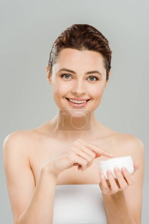 Photo for Happy woman smiling while holding container with face cream isolated on grey - Royalty Free Image