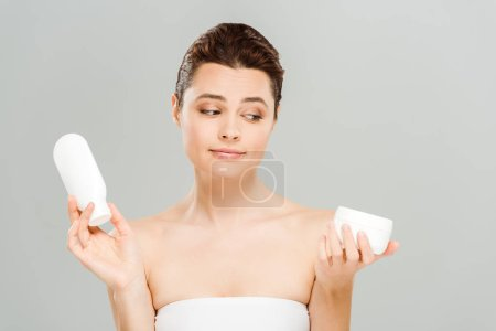 Photo for Attractive woman looking at container with cosmetic cream and holding bottle of body lotion isolated on grey - Royalty Free Image