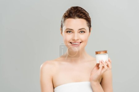 Photo pour Récipient heureux de fixation de femme avec la crème de visage d'isolement sur le gris - image libre de droit