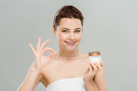cheerful woman showing ok sign and holding face cream isolated on grey