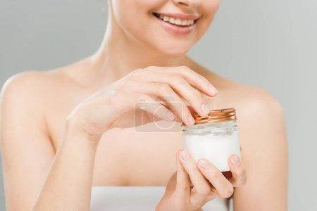 Photo pour Vue recadrée de récipient heureux de fixation de femme avec la crème cosmétique d'isolement sur le gris - image libre de droit