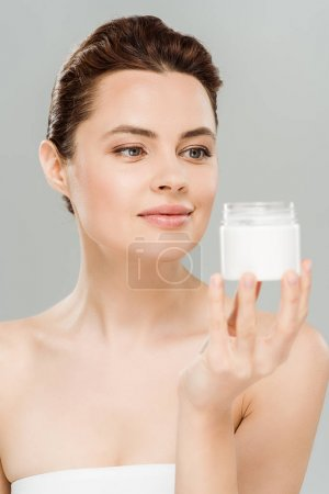 Photo for Happy woman looking at container with cosmetic cream isolated on grey - Royalty Free Image