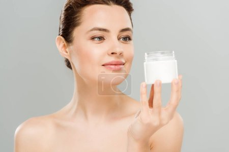 Photo for Cheerful naked woman looking at container with cosmetic cream isolated on grey - Royalty Free Image