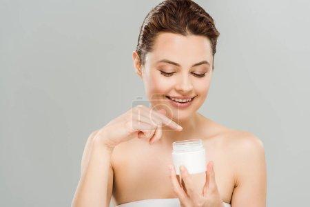 Photo pour Femme heureux pointant avec le doigt au récipient avec la crème de visage d'isolement sur le gris - image libre de droit