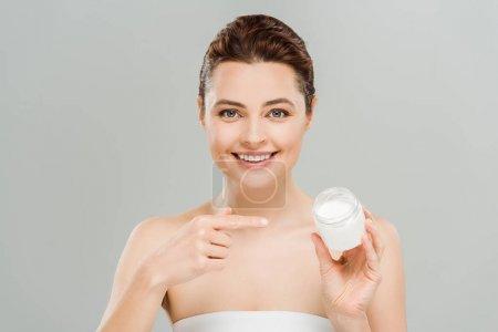 Photo pour Femme heureux pointant avec le doigt au récipient avec la crème de visage et regardant l'appareil-photo isolé sur le gris - image libre de droit