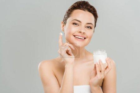 Photo pour Récipient heureux de fixation de femme avec la crème de visage et regardant l'appareil-photo isolé sur le gris - image libre de droit